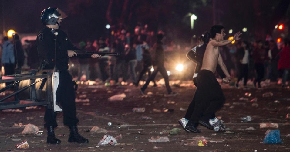 Policial aponta arma em direção à manifestantes após confusão eclodir na região central de Buenos Aires