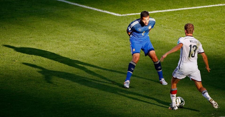 Thomas Muller tenta passar por Garay na final da Copa do Mundo, entre Alemanha e Argentina, no Maracanã