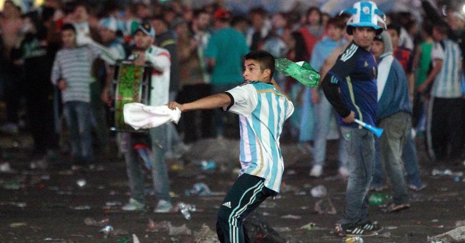 Torcedor argentino atira objeto em direção à polícia durante confusão no centro de Buenos Aires após final da Copa do Mundo