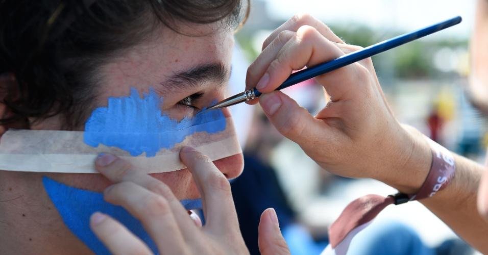 Torcedor da Argentina acerta os últimos preparativos para a final: a pintura facial