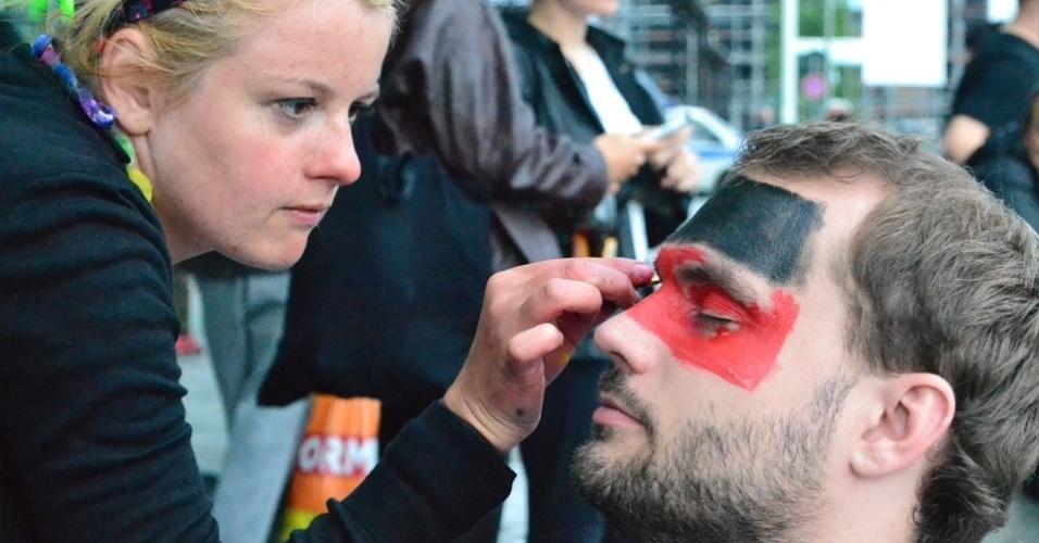 13.jul.2014 - Na frente da estação de metrô, torcedora pinta rostos de voluntários com a bandeira alemã