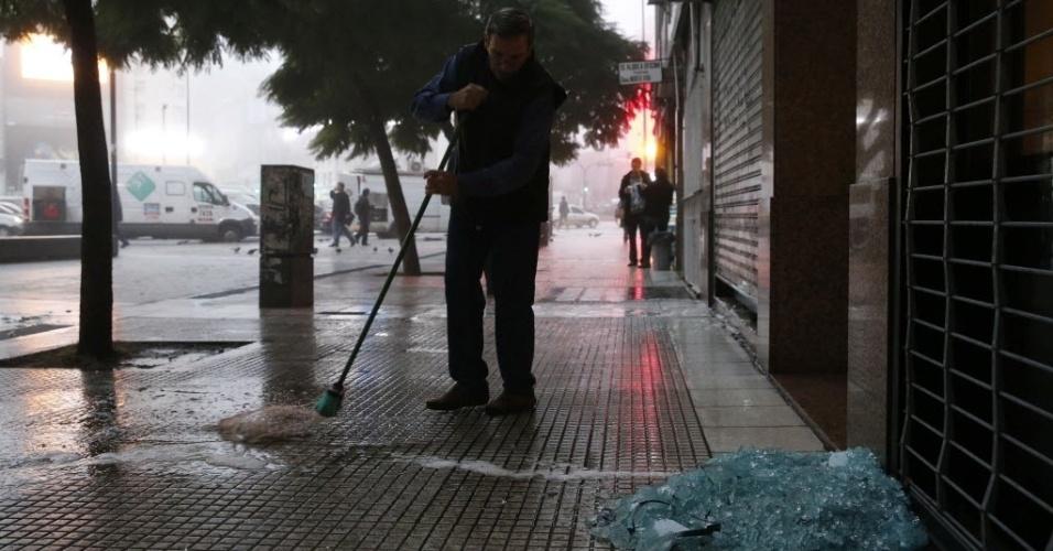 14.jul.2014 - Homem varre cacos de vidro na calçada no centro de Buenos Aires, resultado da quebradeira proporcionada por torcedores revoltados com a derrota da Argentina na final da Copa do Mundo