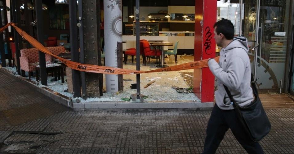 14.jul.2014 - Pedestre observa quebradeira em restaurante na manhã desta segunda-feira (17/07), resultado da revolta de torcedores argentinos com a derrota na final da Copa