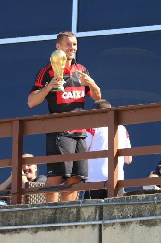 14.jul.2014 - Vestindo camisa do Flamengo, Podolski mostra taça da Copa do Mundo para torcedores em sacada do hotel onde a Alemanha está hospedada no Rio de Janeiro