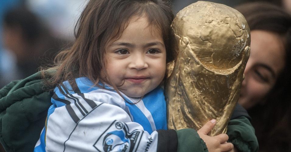Criança argentina segura uma réplica da taça da Copa do Mundo na recepção aos vice-campeões mundiais