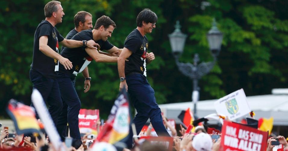 Comissão técnica da seleção da Alemanha caminha sobre o palco da comemoração do título