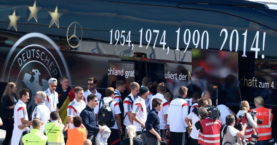 Elenco campeão do mundo da Alemanha embarca no ônibus após a chegada a Berlim. O veículo foi personalizado com os anos das conquistas do país na Copa do Mundo