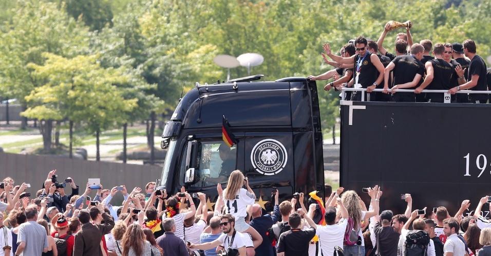 Em carro aberto, jogadores da Alemanha exibe taça da Copa do Mundo em meio a multidão em Berlim
