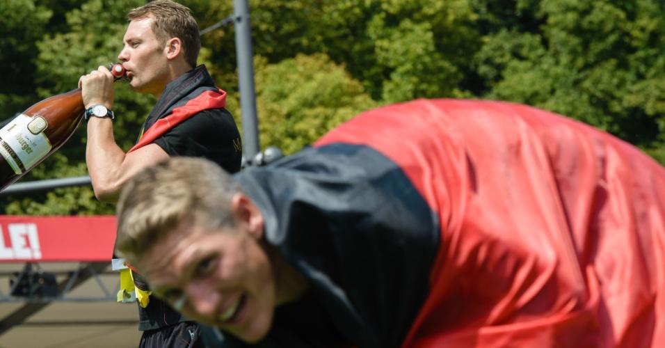 Goleiro Neuer bebe cerveja em garrafa gigante enquanto Schweinsteiger interage com torcedores