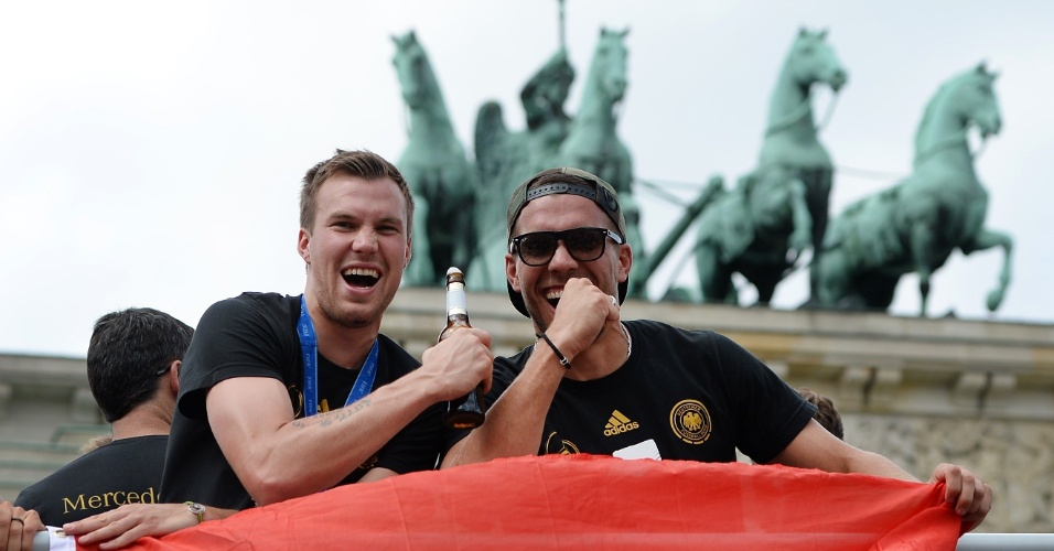 """Ein prosit! Ou """"um brinde"""", em português. Com cerveja na mão, Kevin Grosskreutz e Lukas Podolski chegam ao palco de comemoração do título, em frente ao Portão de Brandenburgo"""
