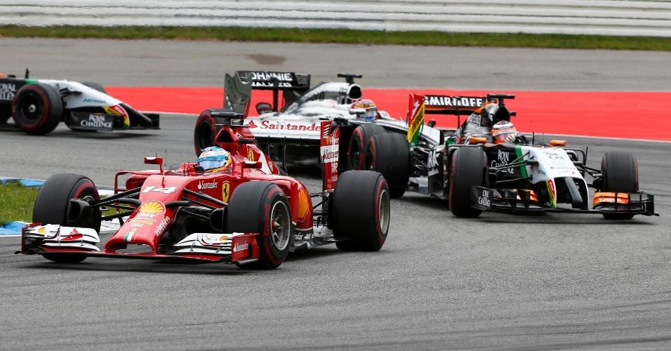 20.jul.2014 - Fernando Alonso, da Ferrari, tenta manter a posição no início do GP da Alemanha. Nico Rosberg venceu a corrida