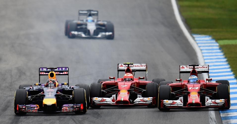 20.jul.2014 - Sebastian Vettel (esquerda), Kimi Raikkonen (centro) e Fernando Alonso fazem bela briga de posição durante o GP da Alemanha, vencido por Nico Rosberg