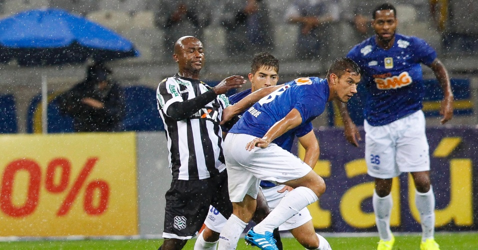 26 jul 2014 - Zagueiro Dedé (observando o lance ao fundo) voltou a jogar pelo Cruzeiro após dois meses fora em tratamento de lesão
