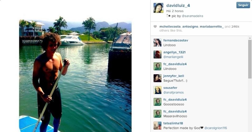 26.jul.2014 - Usando bermuda da CBF, David Luiz pratica stand up paddle junto com a namorada, Sara Madeira, que tirou sua foto