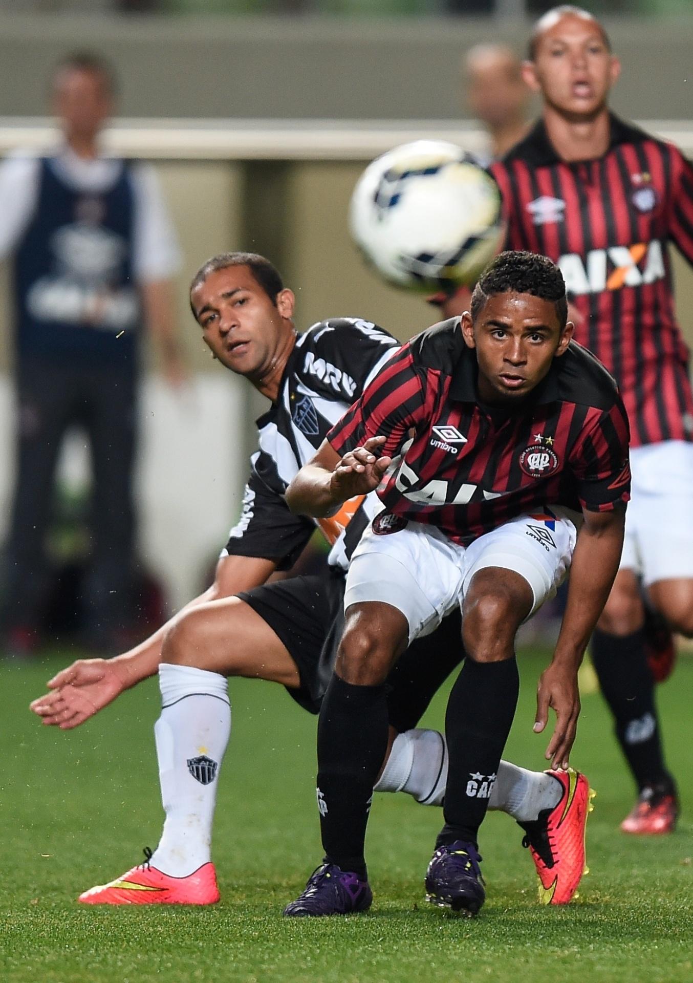Pierre e Deivid disputam a bola no jogo entre Atlético-MG e Atlético-PR