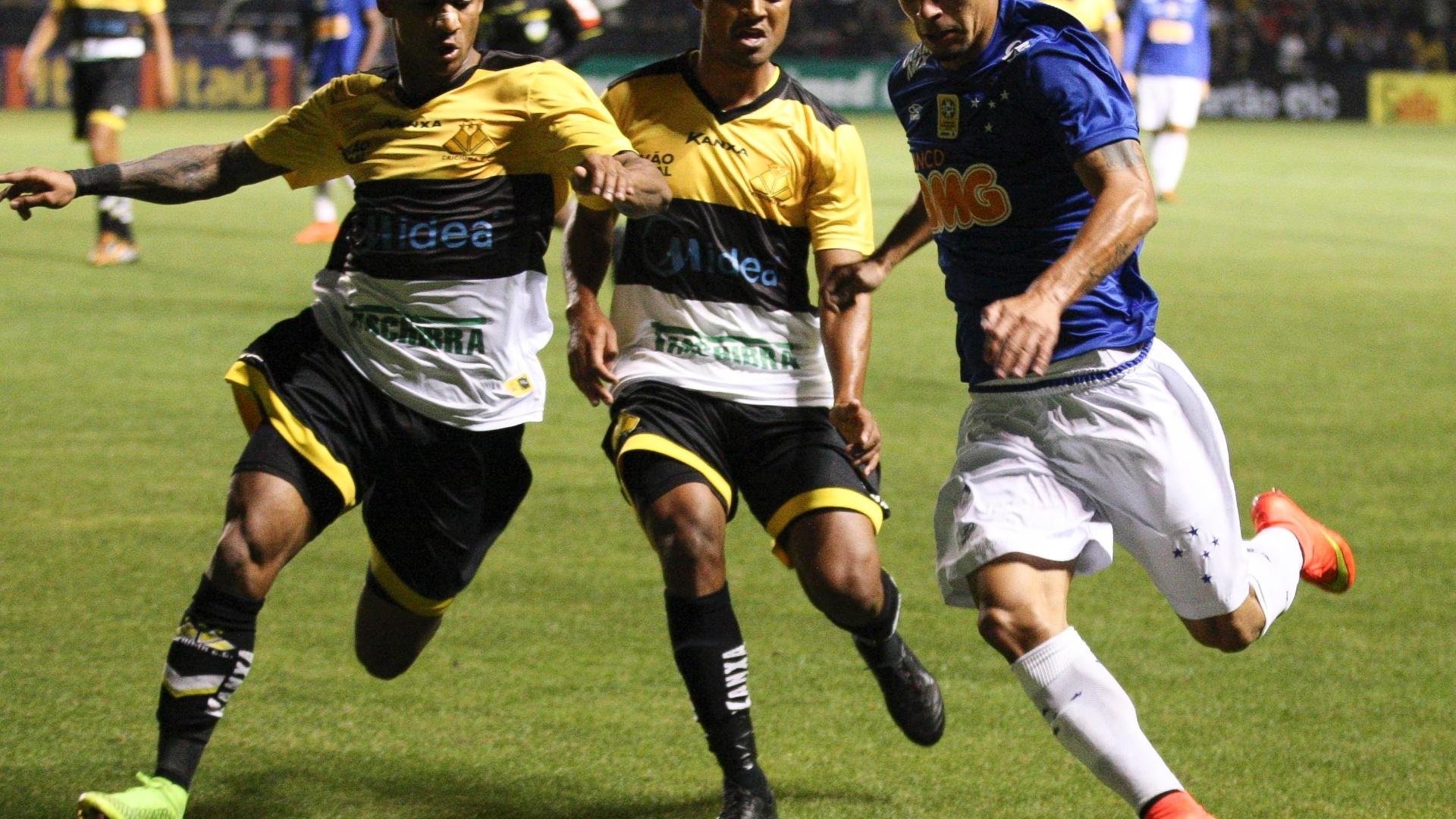 Egídio, do Cruzeiro, tenta jogada pela esquerda contra a marcação de Eduardo e Gualberto, do Criciúma