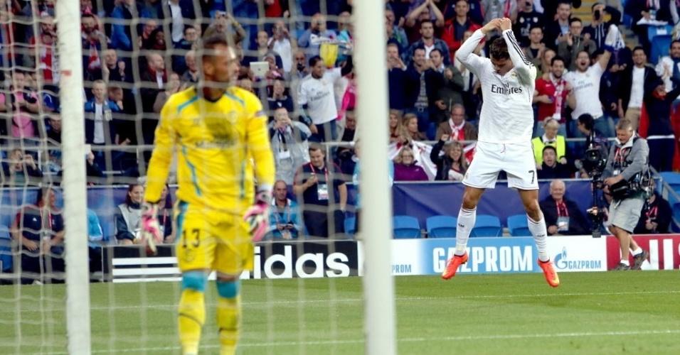 Beto, goleiro do Sevilla, busca a bola no gol e, ao fundo, Cristiano Ronaldo comemora o gol que abriu o placar para o Real Madrid