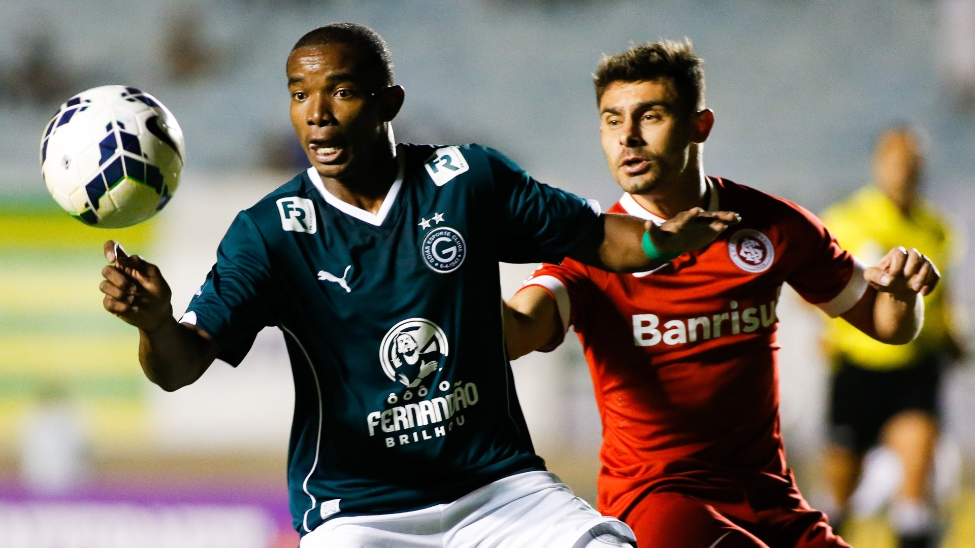 Thiago Mendes, do Goiás, tenta dominar a bola marcado de perto por Alex, do Internacional