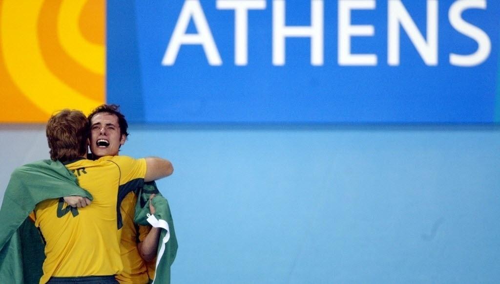 Enrolado na bandeira do Brasil, Ricardinho abraça o meio de rede André Heller na comemoração do título olímpico em 2004