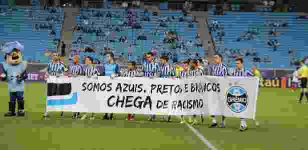 Jogadores do Grêmio entram em campo para o jogo com o Bahia com faixa contra o racismo - Divulgação/Grêmio