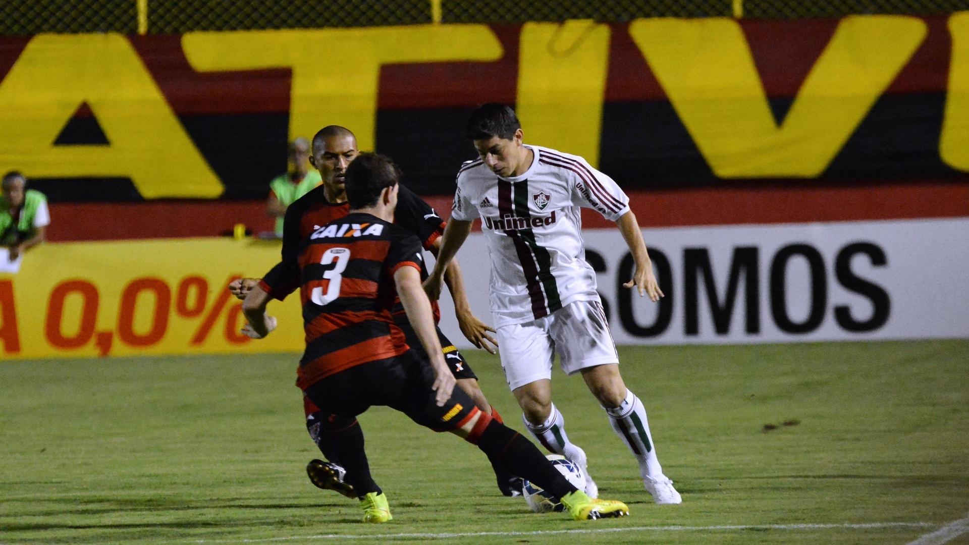 Conca tenta driblar zagueiro do Vitória em partida do Fluminense pelo Brasileirão
