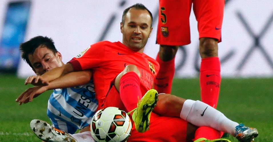 Iniesta sofre dura marcação durante o jogo do Barcelona contra o Málaga