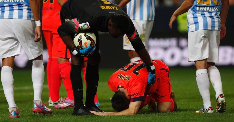 Lionel Messi, atacante do Barcelona, cai no gramado após ser atingido pelo brasileiro Weligton, do Málaga, no Campeonato Espanhol