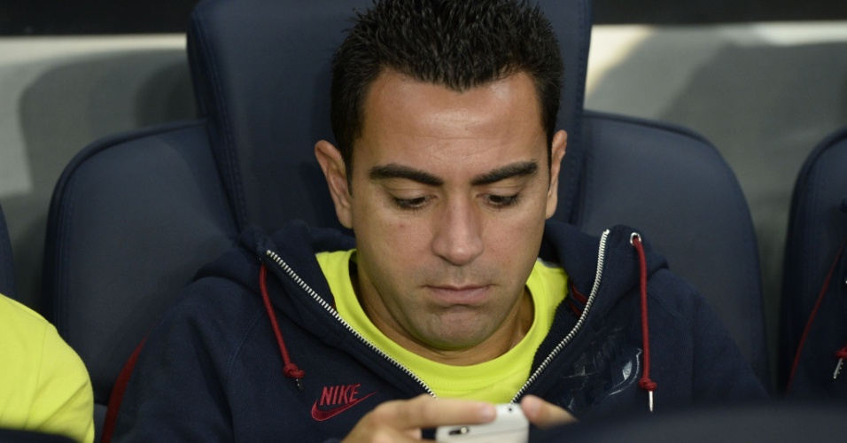 Xavi, meia do Barcelona, mexe no celular antes do jogo contra o PSG, em Paris, pela Liga dos Campeões