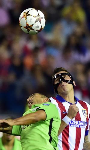 Tevez (verde) e Mandzukic (máscara) disputam bola durante o jogo entre Juventus e Atlético de Madri