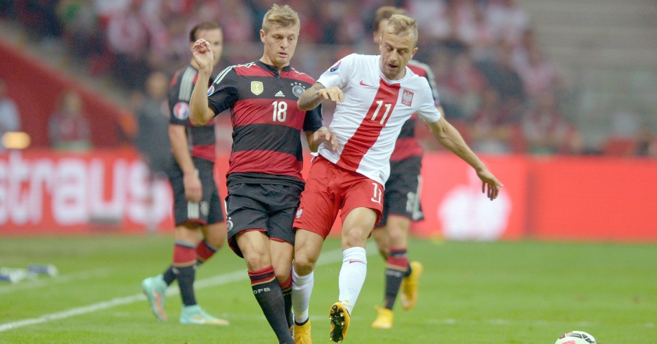 Toni Kroos, meia da Alemanha, disputa a bola com Kamil Grosicki, da Polônia, em jogo válido pelas Eliminatórias da Euro 2016