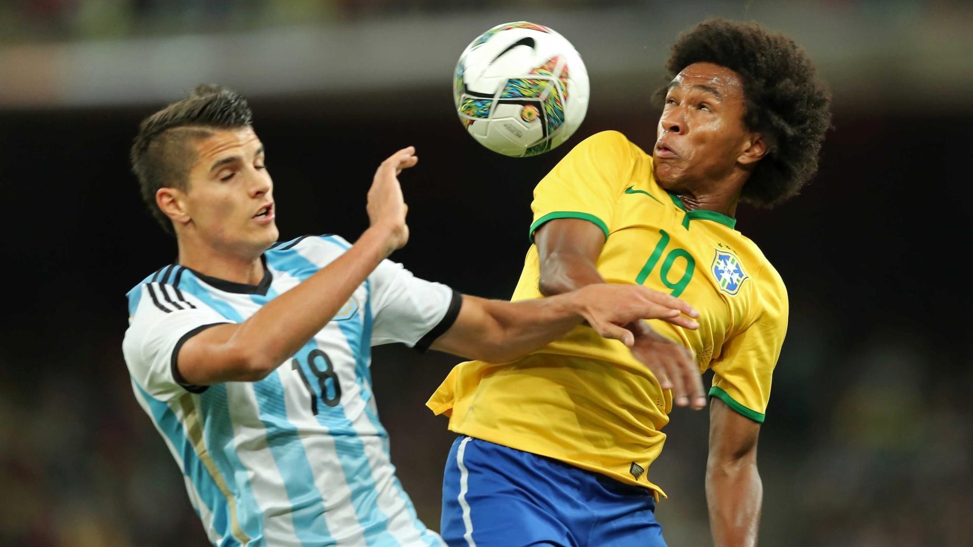 Willian, meia da seleção, sobe para brigar de cabeça com Lamela, da Argentina, no Superclássico das Américas, em Pequim