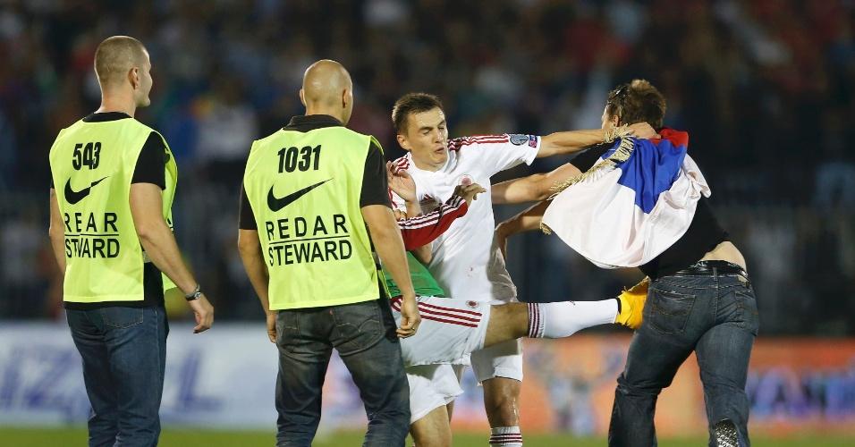 Burim Kukeli (centro) tenta separar briga entre um torcedor e seu companheiro de equipe