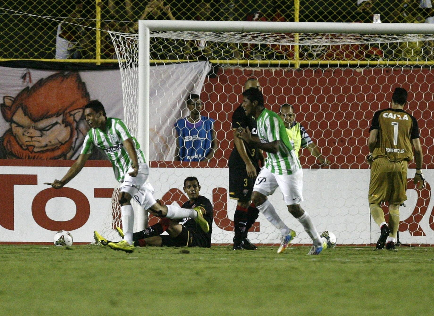 16. out. 2014 - Goleiro Fernandez, do Vitória, acaba sentado após tomar ol de Daniel Bocanegra, do Atlético Nacional, que eliminou o Vitória da Copa Sul-Americana
