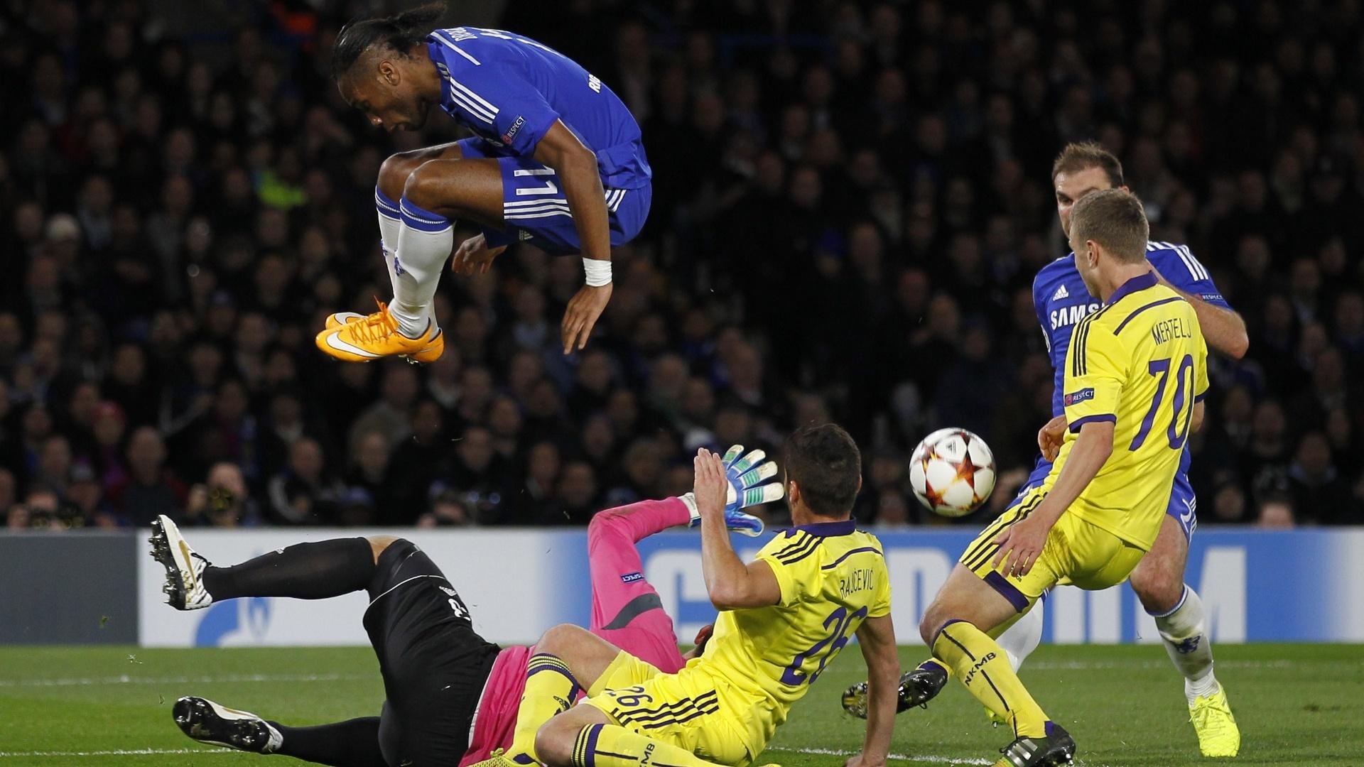 Didier Drogba, atacante do Chelsea, salta para evitar um choque com os jogadores do Maribor, pela Liga dos Campeões