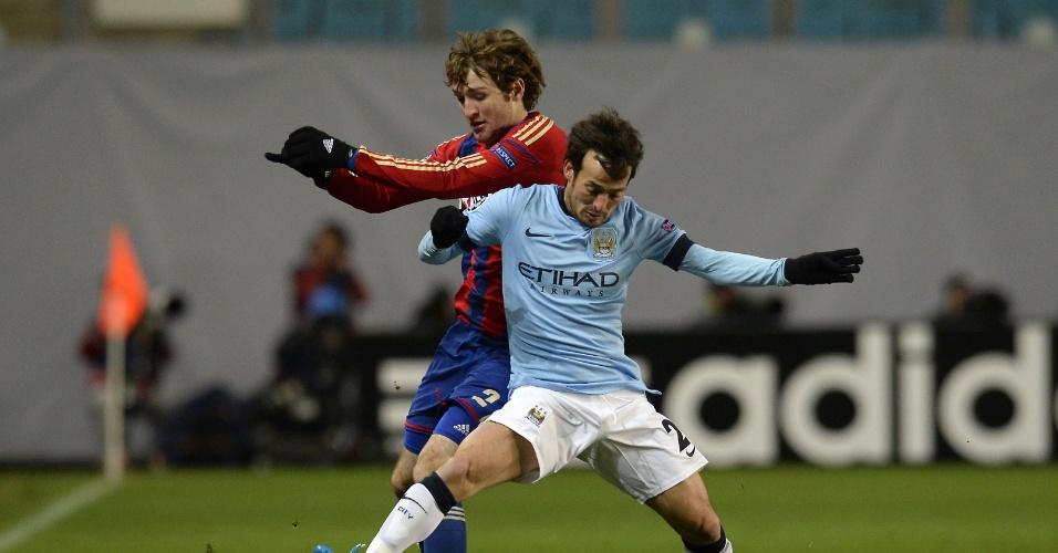 Mário Fernandes (vermelho) tenta roubar a bola de David Silva, do Manchester City