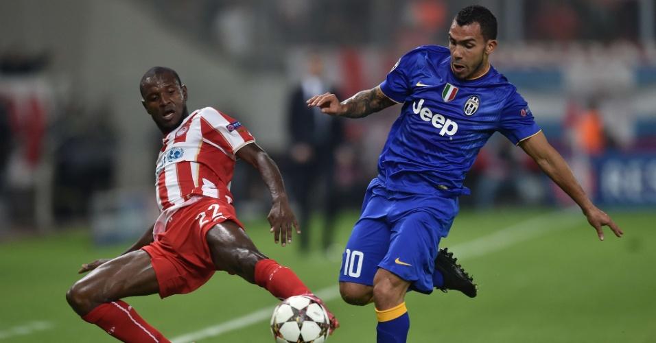 Abidal (vermelho) e Tevez (azul) disputam a bola durante jogo entre Olympiacos x Juventus