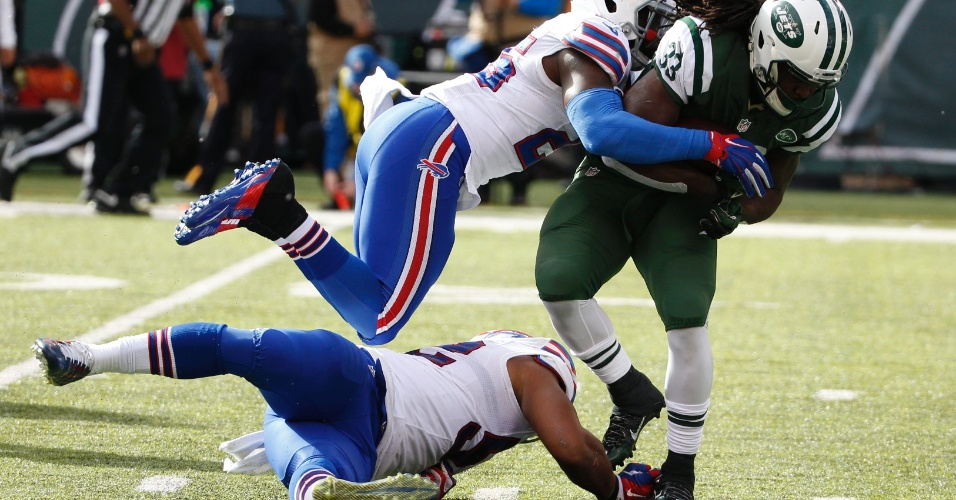 Chris Ivory, do New York Jets, tenta passar por dois marcadores do Buffalo Bills