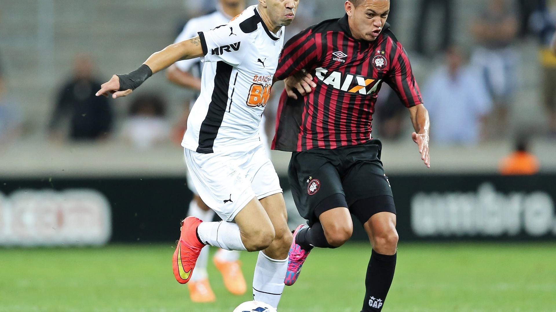 Diego Tardelli disputa bola com jogador do Atlético-PR em jogo do Atlético-MG