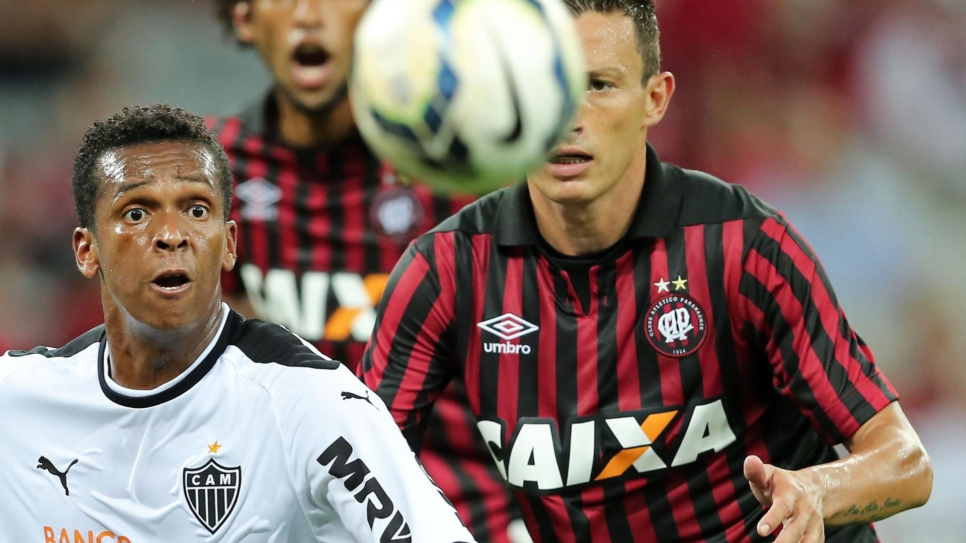 Jô disputa bola com Gustavo no jogo entre Atlético-MG e Atlético-PR