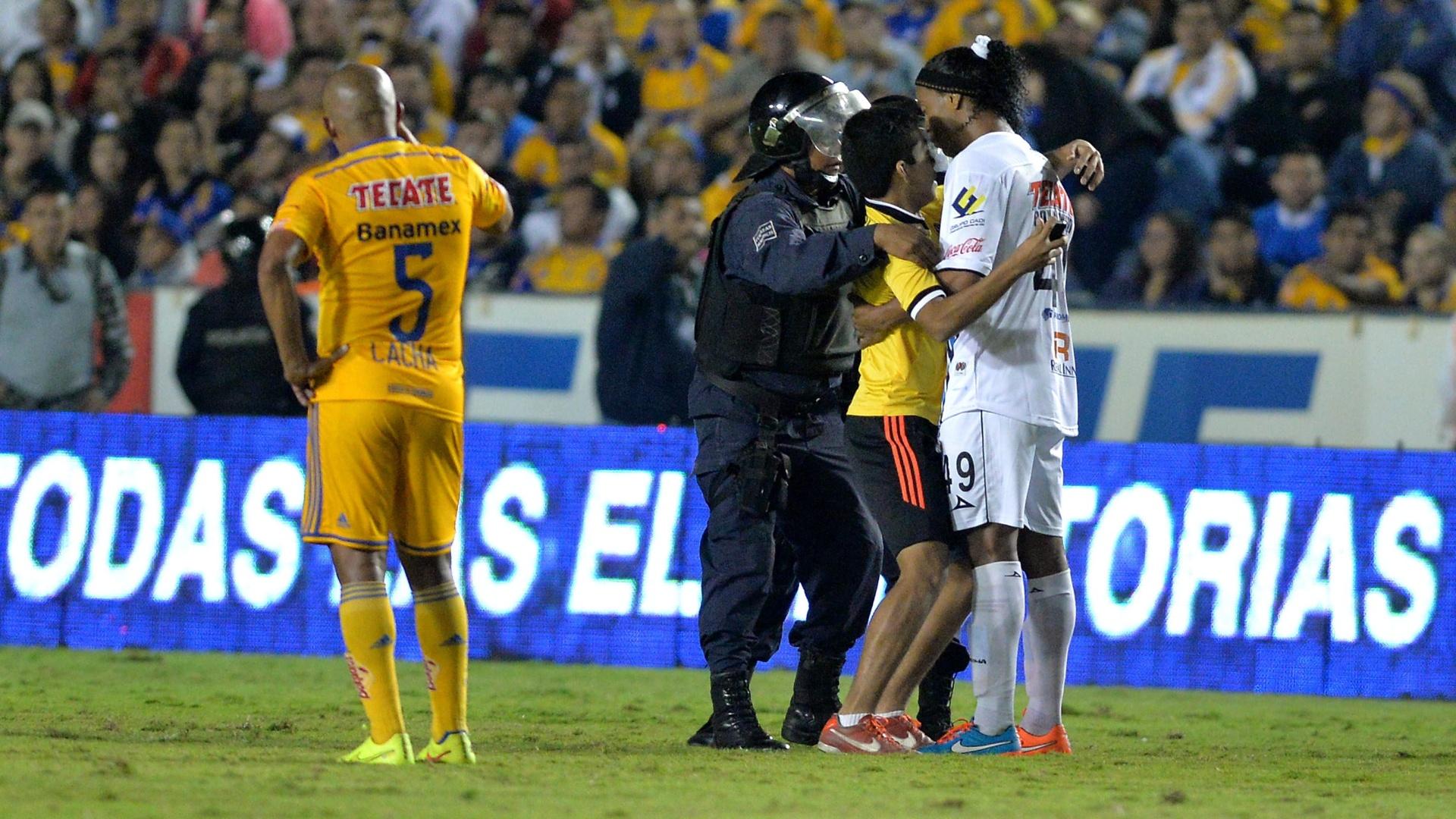 Ronaldinho é abraçado por invasor durante partida do Campeonato Mexicano em que seu time, o Querétaro, perdeu para o Tigres por 1 a 0