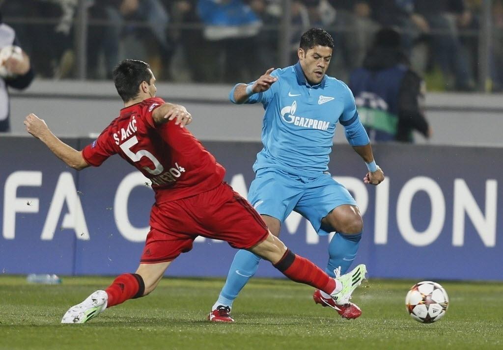 Hulk (azul) tenta passar pela marcação de Spahic (vermelho) durante jogo da Liga dos Campeões