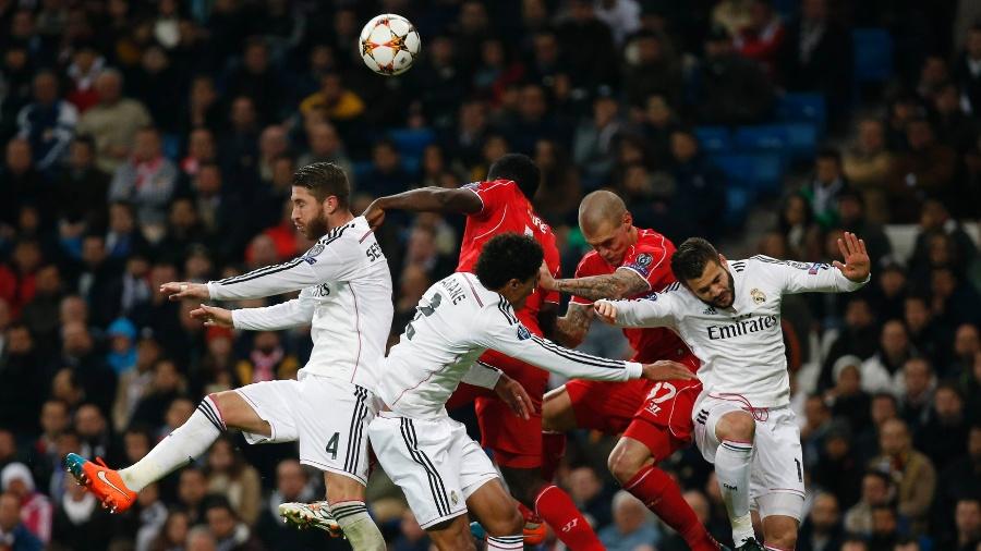 Jogadores de Real Madrid e Liverpool brigam pela bola em jogo da Liga dos Campeões - REUTERS/Susana Vera