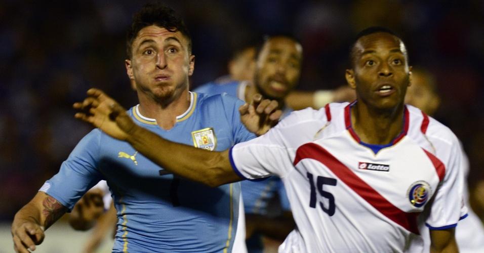 13.nov.2014 - Cristian Rodriguez (esq), do Uruguai, disputa pela bola com o costarriquenho Junior Diaz durante amistoso no Centenário, em Montevidéu