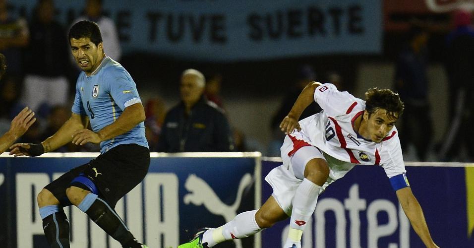 13.nov.2014 - Suárez observa enquanto Bryan Ruiz passa com a bola no amistoso entre Uruguai e Costa Rica em Montevidéu