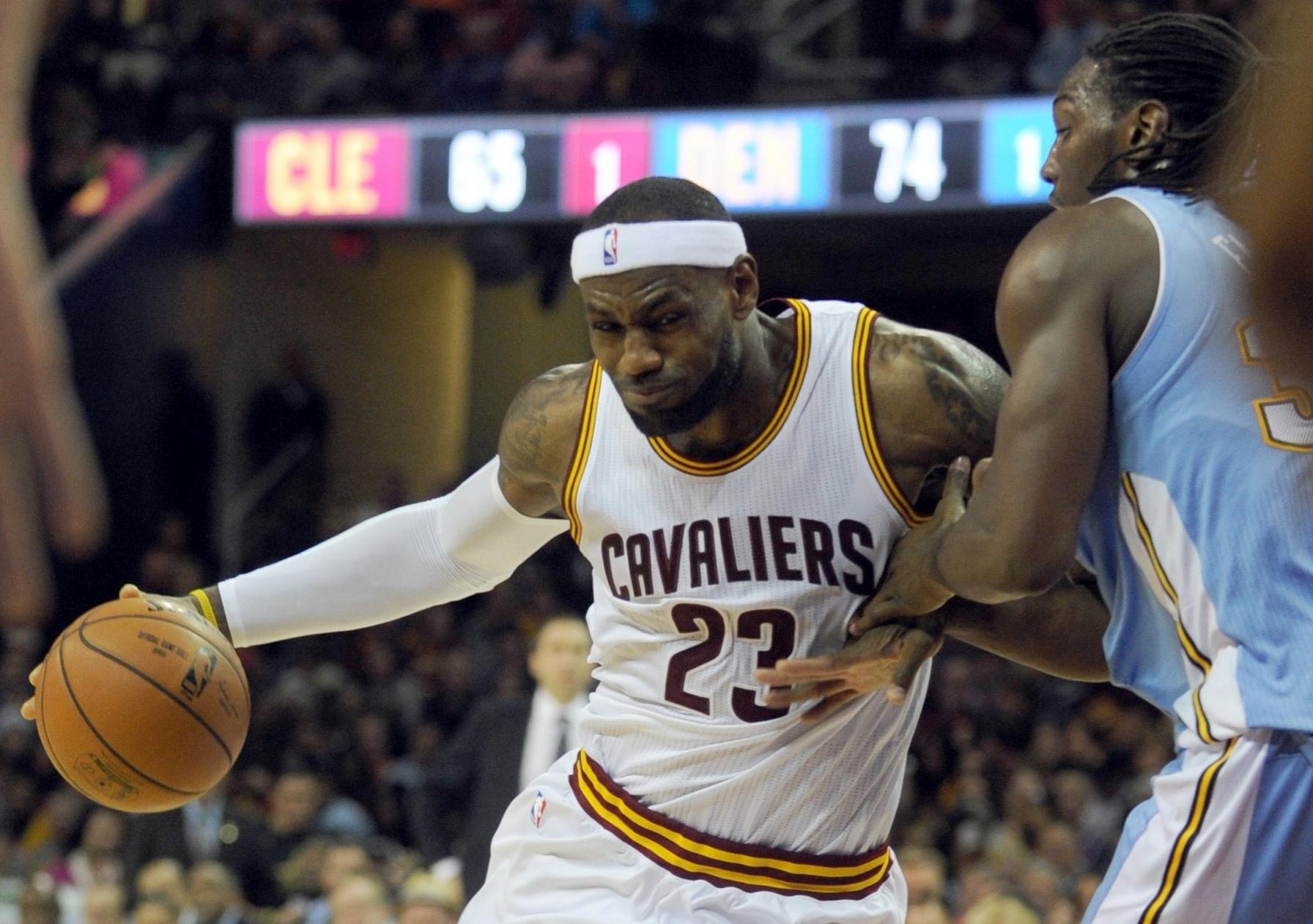 17.nov.2014 - LeBron James tenta passar pela marcação na derrota do Cleveland Cavaliers para o Denver Nuggets