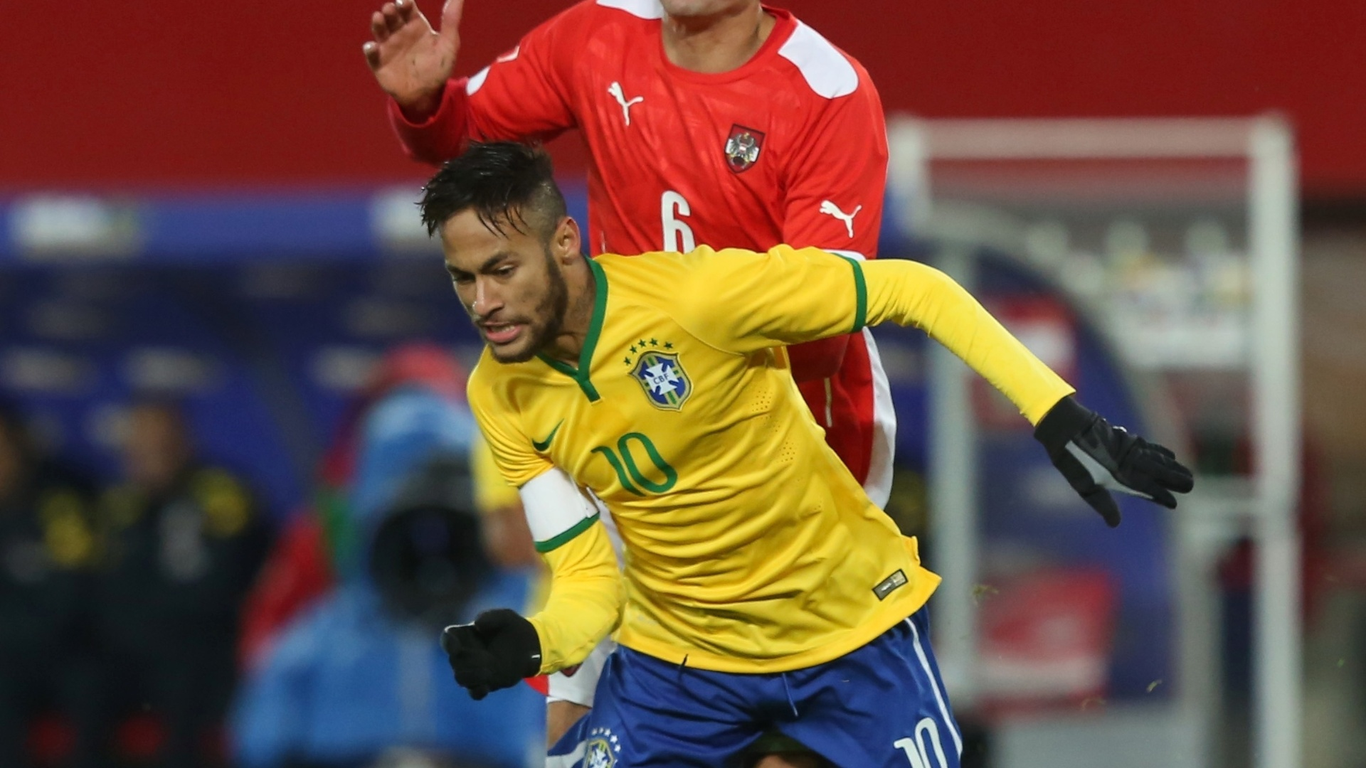 Neymar (frente) tenta superar a marcação do austríaco Ilsanker durante amistoso do Brasil