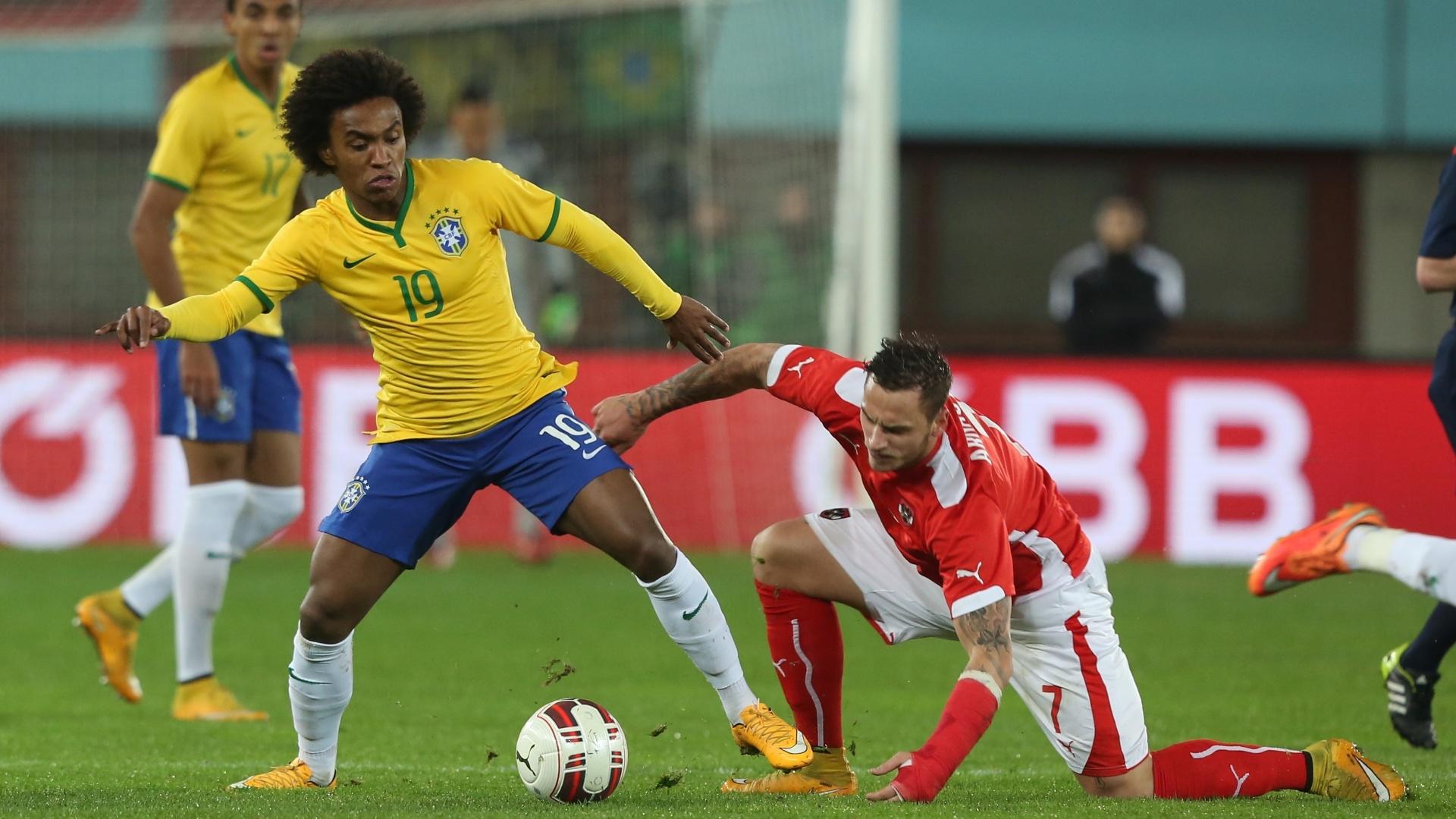 Willian (em pé) disputa bola com Arnautovic durante amistoso do Brasil contra a Áustria