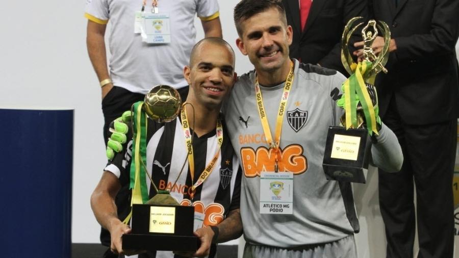 Diego Tardelli mostra o troféu de melhor jogador e Victor o de melhor goleiro da Copa do Brasil - EFE/Paulo Fonseca