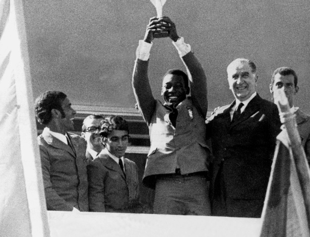 Pelé levanta a Taça Jules Rimet após conquistar a Copa do Mundo de 1970 ao lado do presidente Emílio Médici