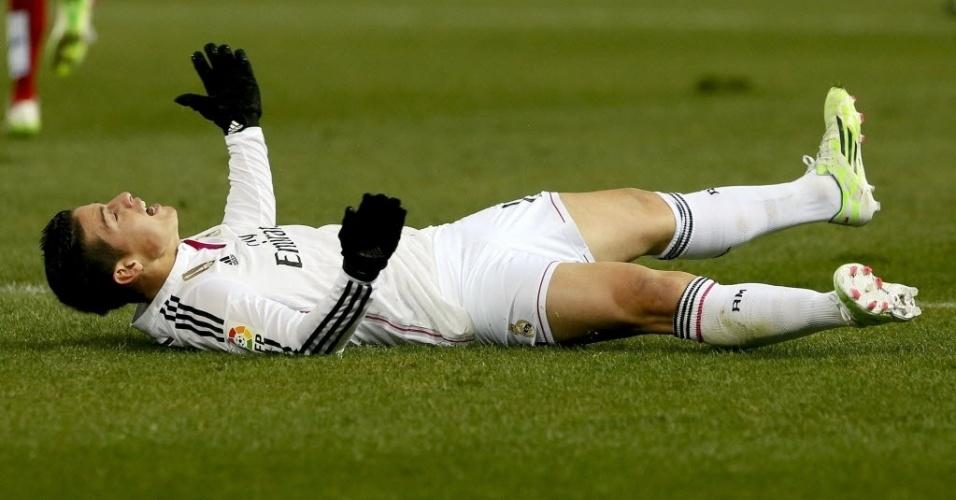 Colombiano James Rodríguez se lamenta deitado no chão durante o clássico de Madrid, no jogo de ida das oitavas de final da Copa do Rei